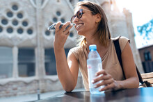 Woman Smiling While Talking On Mobile Phone While Sitting Against Sagrada Familia At Barcelona, Catalonia, Spain