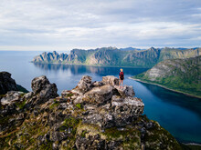 Female Hiker Looking At View Standing On Mountain At Husfjellet, Senja, Norway