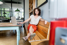 Businesswoman Using Laptop While Sitting On Bench At Office