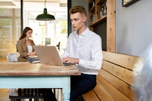 Businessman Working On Laptop While Sitting With Colleague In Background At Office
