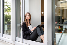 Young Businesswoman With Digital Tablet Looking Away While Sitting At Office Door