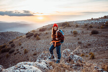 Smiling Female Hiker Looking Away While Standing On Rock Mountain During Sunset