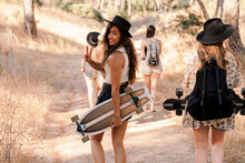 Woman With Skateboard Showing Peace Gesture While Walking With Friends On Forest Path