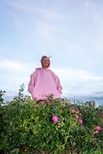 YoungÔøΩwoman With Pink Hair Wearing Pink Hooded Shirt Near Rose Bush