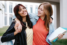 Smiling Young Student With Arm Around Looking At Friend In Campus