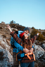 Happy Boyfriend Embracing Girlfriend Standing With Arms Outstretched On Mountain During Vacation