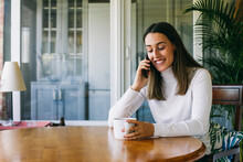 Smiling Woman With Coffee Cup Talking On Mobile Phone While Sitting At Home