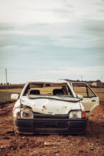 White Wrecked Car Abandoned In Middle Of Field