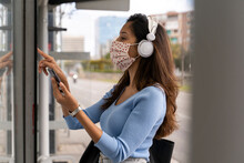 Woman In Face Mask Wearing Headphones While Purchasing Bus Ticket During COVID-19