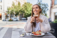 Smiling Woman Looking Away While Sitting At Sidewalk Cafe