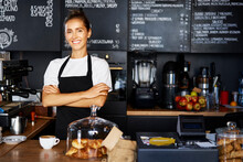 Portrait Of Smiling Waitress With Arms Crossed Working At Cafe