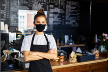 Portrait Of Waitress In Protective Face Mask With Arms Crossed Standing At Cafe