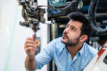 Male Entrepreneur Concentrating While Analyzing Robotic Arm In Manufacturing Factory