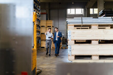 Businessman And Colleague Inspecting Warehouse While Walking At Factory