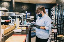 Female Chef Using Smart Phone While Standing At Kitchen Counter In Restaurant During Coronavirus