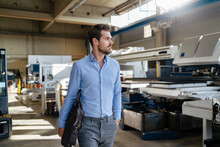 Male Entrepreneur With Brief Case Walking At Factory