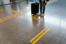 Woman With Luggage Waiting Her Turn By Sign On Flooring At Subway Station