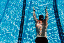 Young Man Gliding Underwater After Diving Into Pool