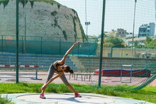 Young Woman Doing Fitness Training In Local Sports Stadium Outdo