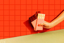 Female Hand Holding Chocolate Bars Against Red Tile Wall