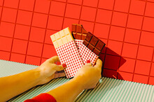 Woman Hands Holding Chocolate Bars Against Red Tile Wall