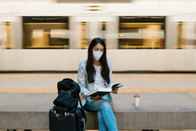 Woman Reading Book While Sitting Against Moving Train At Metro Station