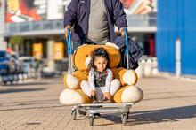 Cute Girl Sitting With Teddy Bear In Luggage Cart On Footpath