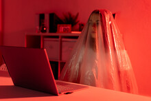 Worried Woman Covered In Plastic Sitting With Laptop At Desk In Home Office During Coronavirus Crisis
