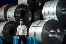 Male Owner With Hand In Pocket Standing Against Steel Rolls In Industry
