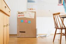 Cardboard Box Used To Create Makeshift Home Office On Dining Room Floor
