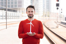Smiling Entrepreneur Holding Wind Turbine On Railroad Station Platform