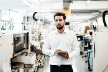 Confident Businessman Holding Digital Tablet Standing In Bright Industry
