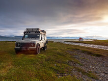 Off-road Car Parked In Front Of Icelandic River At Cloudy Sunset With Secluded Unadsdalskirkja Church In Background