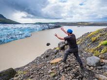 Mid Adult Man Throwing Stone In Lake At Svinafellsjokull Glacier, Iceland