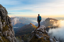 Pensive Hiker Looking At View While Standing On Mountain Peak During Sunrise At Bergamasque Alps, Italy