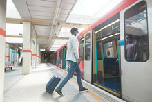Male Entrepreneur Business Travel Boarding Metro Train At Station During Pandemic