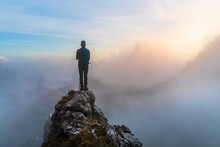 Pensive Male Hiker Standing On Mountain Peak During Sunrise At Bergamasque Alps, Italy