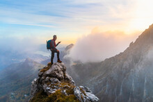 Pensive Hiker Using Smart Phone On Mountain Peak During Sunrise At Bergamasque Alps, Italy