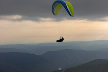 Aerial View Of Male Paraglider Soaring Above Mountains At Dusk