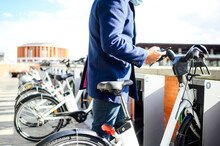 Man Unlocking Bicycle Through Smart Phone On Sunny Day During COVID-19