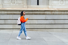 Young Woman With Backpack And Mobile Phone Looking Away While Walking On Footpath