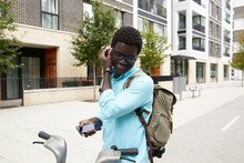 Smiling Man Wearing Earphones While Holding Smart Phone Standing On Bicycle Lane In City