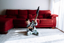 Happy Boy Playing Guitar While Kneeling Against Sofa In Living Room