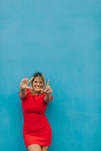 Woman Making Frame Formation With Hands Against Blue Wall