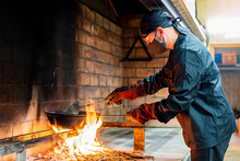 Traditional Cooking Of Paella In Restaurant Kitchen, Chef Wearing Protective Mask