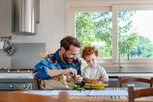 Smiling Man Looking At Son Holding Pea In Kitchen
