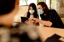 Man And Woman Wearing Masks While Sharing Digital Tablet In Restaurant
