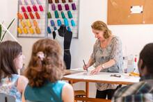 Senior Designer Drawing At Workbench While Teaching To Coworker At Design Studio