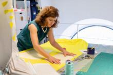 Female Fashion Designer Adjusting Yellow Fabric At Workbench In Atelier