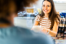 Happy Female Owner Selling Coffee To Woman In Cafe